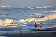 Indonesia, Bali, two women carrying surfboards at seafront - KNTF000005