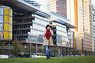 Germany, Berlin, young woman wearing black hat and red scarf telephoning with smartphone - MMFF000835