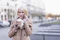 Germany, Berlin, young woman with coffee to go telephoning with smartphone - MMFF000844