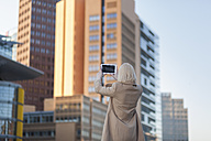 Germany, Berlin, young woman photographing with phablet - MMFF000847