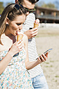 Young couple with ice cream cone and smartphone outdoors in summer - UUF003870