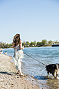 Germany, Mannheim, young woman walking with dog at River Rhine - UUF003931