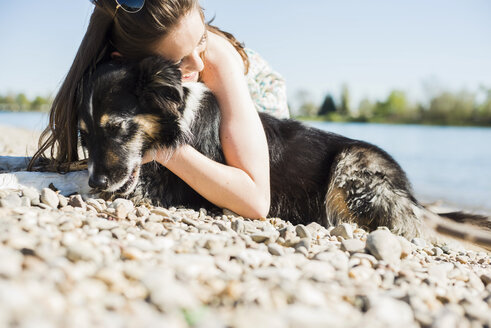 Germany, Mannheim, young woman cuddling with dog at River Rhine - UUF003936