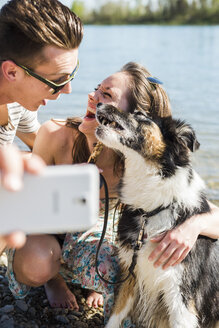 Happy young couple taking selfie with dog by the riverside - UUF003938