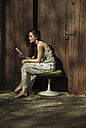 Young woman sitting on old stool holding cell phone - UUF003871