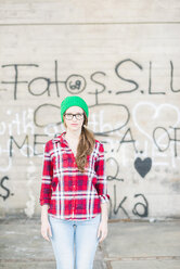 Young woman with checkered shirt and green wooly hat at graffiti wall - UUF003906
