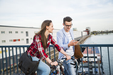 Germany, Mannheim, young man and woman with bicycle and cell phone on bridge - UUF003913