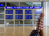 Germany, Frankfurt, traveller and display panel at airport - AM003985