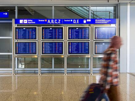 Germany, Frankfurt, traveller and display panel at airport - AM003985