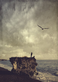 Spain, La Palma, Man standing on rock and looking out on the sea - DWI000475