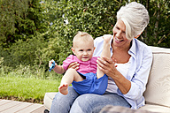 Happy grandmother with baby girl outdoors - MFRF000199