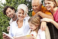 Happy extended family with book outdoors - MFRF000168