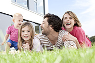 Happy family lying on lawn - MFRF000171