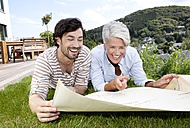 Adult son and mother lying on lawn looking at construction plan - MFRF000177