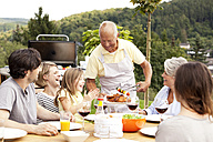 Grandfather serving food from barbecue grill for family at garden table - MFRF000203