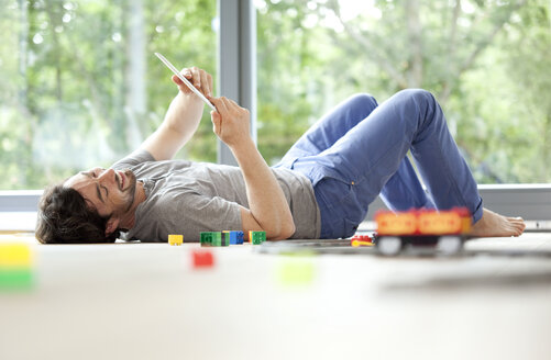 Smiling man lying on floor with digital tablet next to toy train - MFRF000188