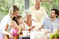 Happy granddaughter with her family reading letter at breakfast table - MFRF000215
