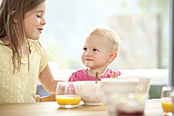 Baby girl with sister at breakfast table - MFRF000218
