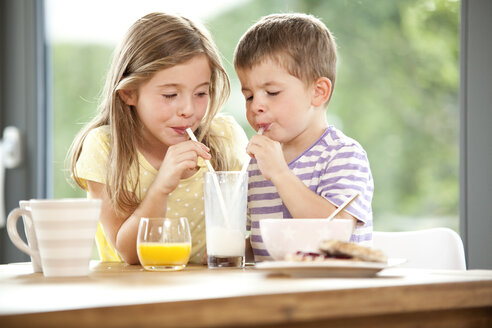 Brother and sister sharing glass of milk - MFRF000197