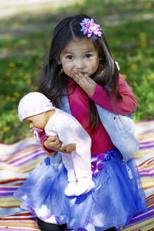 Little girl outdoors playing with a doll - GDF000710