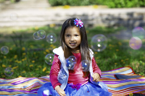 Little girl outdoors surrounded by saop bubbles - GDF000712