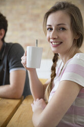 Portrait of smiling young woman drinking coffe from cup - FKF000944