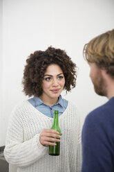 Young woman holding beer bottle looking at man - FKF000956