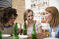 Happy female friends sitting at dining table with beer bottles - FKF001021