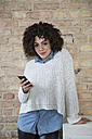 Portrait of young woman with cell phone at brick wall - FKF000972