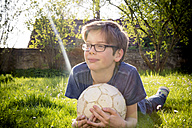 Portrait of boy lying on a meadow with soccer ball - LVF003257