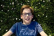 Portrait of boy wearing glasses lying on a meadow - LVF003254