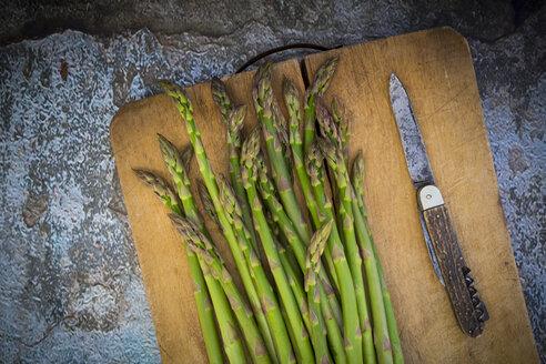 Organic green asparagus on chopping board, knife - LVF003252