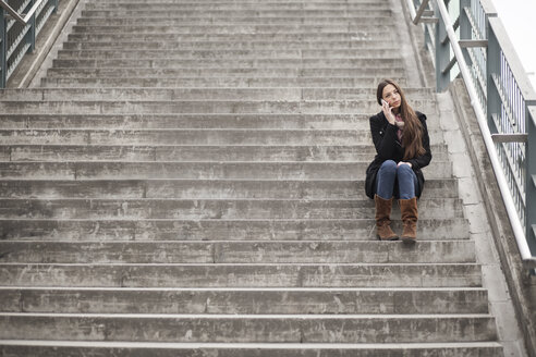 Young woman sitting on stairs telephoning with smartphone - MMFF000704