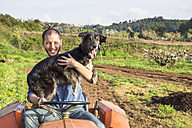 Farmer with tractor on field holding dog - GEMF000229