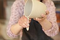 Potter in workshop working on earthenware pot - MAEF010355