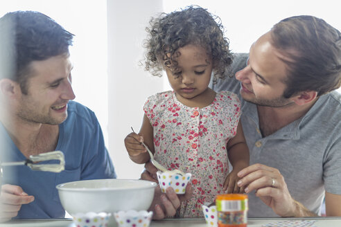 Gay couple with daughter making a cake - ZEF004279