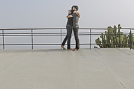 Gay couple hugging each other on a balcony - ZEF004301