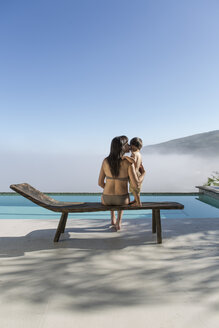 Woman with baby on a lounge next to pool - ZEF004311
