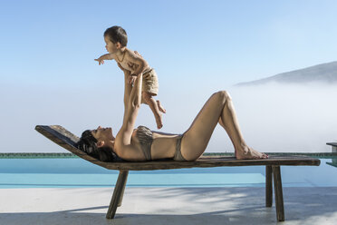 Woman with baby on a lounge next to pool - ZEF004313