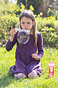 Girl crouching on a meadow blowing big soap bubble - SARF001754