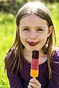 Portrait of girl with ice lolly licking lips - SARF001790