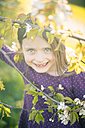 Portrait of smiling little girl looking through twigs of a blossoming tree - SARF001798