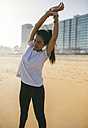 Spain, Gijon, young woman stretching on the beach - MGOF000211