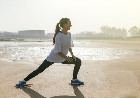 Spain, Gijon, young woman stretching on the beach - MGOF000212