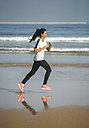 Spain, Gijon, young woman running on the beach - MGOF000207