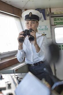 Deck officer on ship holding binoculars - ZEF005489