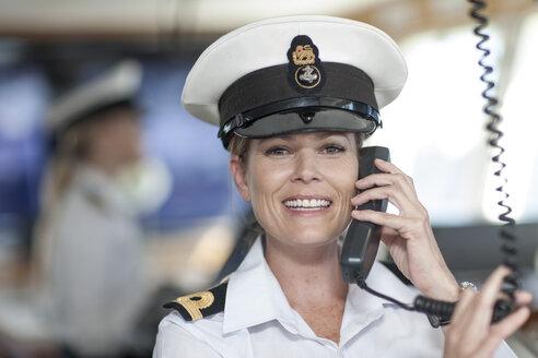 Chief mate on bridge talking on radio - ZEF005493