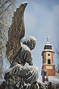 Germany, Mainau, angel statue with castle church in background - KEB000146
