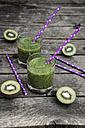 Green smoothie with kiwi, banana and mache, drinking straws, wood - SARF001751