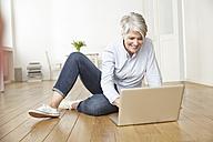 Mature woman sitting on floor using laptop - FMKF001455